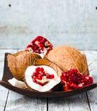 Φρέσκια καρύδα και κόκκινος γρανάτης σε ένα ξύλινο κύπελλο, μπλε υπόβαθρο Στοκ εικόνες με δικαίωμα ελεύθερης χρήσης