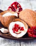 Φρέσκια καρύδα και κόκκινος γρανάτης σε ένα ξύλινο κύπελλο, μπλε υπόβαθρο Στοκ φωτογραφία με δικαίωμα ελεύθερης χρήσης