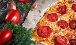 Φρέσκια μαγειρευμένη πίτσα σε χαρτί και τα συστατικά ψησίματος για την πίτσα και σάλτσα στον ξύλινο πίνακα στοκ φωτογραφία