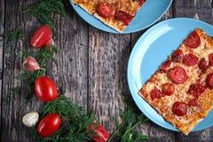 Φρέσκια μαγειρευμένη πίτσα στο μπλε πιάτο και τα συστατικά για την πίτσα και σάλτσα στον ξύλινο πίνακα στοκ εικόνες με δικαίωμα ελεύθερης χρήσης