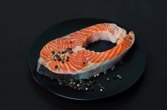 Φρέσκια μπριζόλα σολομών στο μαύρο πιάτο Στοκ Εικόνες