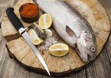 Φρέσκια νορβηγική πέστροφα ουράνιων τόξων με το κόκκινο χαβιάρι λεμονιών, το άλας θάλασσας, το μαχαίρι και τα κρεμμύδια σε ένα ξύ Στοκ Φωτογραφίες
