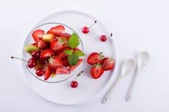 Φρέσκια νόστιμη σαλάτα φρούτων μιγμάτων στο κύπελλο γυαλιού στο άσπρο επιτραπέζιο υπόβαθρο Υγιές πρόγευμα βιταμινών Στοκ Φωτογραφία