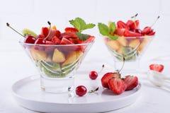 Φρέσκια νόστιμη σαλάτα φρούτων μιγμάτων στο κύπελλο γυαλιού στο άσπρο επιτραπέζιο υπόβαθρο Στοκ Εικόνες