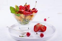 Φρέσκια νόστιμη σαλάτα φρούτων μιγμάτων στο κύπελλο γυαλιού στο άσπρο επιτραπέζιο υπόβαθρο Στοκ φωτογραφία με δικαίωμα ελεύθερης χρήσης