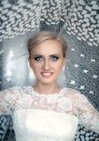 Φρέσκια ξανθή γυναίκα ομορφιάς με τα όμορφα μπλε μάτια στην άσπρη νυφική τοποθέτηση φορεμάτων Στοκ φωτογραφίες με δικαίωμα ελεύθερης χρήσης