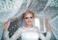 Φρέσκια ξανθή γυναίκα ομορφιάς με τα όμορφα μπλε μάτια στην άσπρη νυφική τοποθέτηση φορεμάτων Στοκ φωτογραφία με δικαίωμα ελεύθερης χρήσης