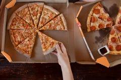 Φρέσκια πίτσα στο κομμάτι λαβής κιβωτίων και χεριών, τοπ άποψη στοκ φωτογραφία με δικαίωμα ελεύθερης χρήσης