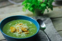Φρέσκια πολτοποιηίδα σούπα με το μπρόκολο και πράσινα φασόλια σε ένα μπλε πιάτο σε ένα ξύλινο υπόβαθρο στοκ εικόνα με δικαίωμα ελεύθερης χρήσης