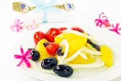 Πορτοκαλιά σαλάτα και λουλούδια γύρω από το πιάτο Στοκ Εικόνες