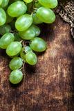 Φρέσκια πράσινη μακροεντολή σταφυλιών Σταφύλια σε έναν εκλεκτής ποιότητας ξύλινο πίνακα Στοκ Φωτογραφίες