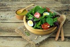 Φρέσκια πράσινη σαλάτα με τα καρύδια πεύκων ντοματών κερασιών και τα αυγά ορτυκιών Σάλτσα σαλάτας κατανάλωση υγιής ενάντια ως δολ Στοκ Εικόνες