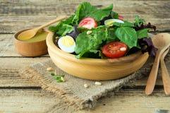 Φρέσκια πράσινη σαλάτα με τα καρύδια πεύκων ντοματών κερασιών και τα αυγά ορτυκιών Σάλτσα σαλάτας κατανάλωση υγιής ενάντια ως δολ Στοκ εικόνα με δικαίωμα ελεύθερης χρήσης