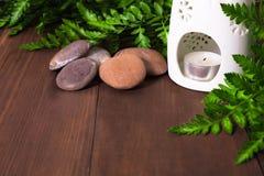 Φρέσκια πράσινη φτέρη, κερί στο λαμπτήρα αρώματος και πέτρες για τη SPA massag στοκ εικόνες με δικαίωμα ελεύθερης χρήσης