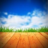 Φρέσκια πράσινη χλόη άνοιξη με το μπλε bokeh και το φως του ήλιου και το ξύλινο φ Στοκ Φωτογραφία