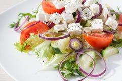 Φρέσκια σαλάτα άνοιξη με το αγγούρι, την ντομάτα, το τυρί και το arugula που απομονώνονται σε ένα άσπρο πιάτο Στοκ Φωτογραφίες
