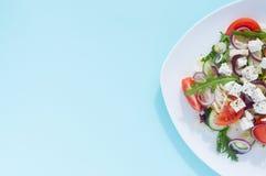 Φρέσκια σαλάτα άνοιξη με το αγγούρι, την ντομάτα, το τυρί και το arugula που απομονώνονται σε ένα άσπρο πιάτο Στοκ Φωτογραφία