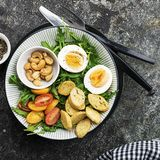 Φρέσκια σαλάτα άνοιξη με το βρασμένο αυγό, το arugula, τη σαλάτα, τις ντομάτες, τα πεκάν και τριζάτα ψημένα croutons ψωμιού σε έν Στοκ εικόνες με δικαίωμα ελεύθερης χρήσης
