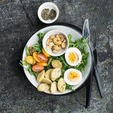 Φρέσκια σαλάτα άνοιξη με το βρασμένο αυγό, το arugula, τη σαλάτα, τις ντομάτες, τα πεκάν και τριζάτα ψημένα croutons ψωμιού σε έν Στοκ εικόνα με δικαίωμα ελεύθερης χρήσης