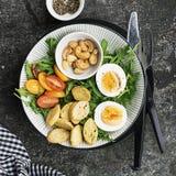 Φρέσκια σαλάτα άνοιξη με το βρασμένο αυγό, το arugula, τη σαλάτα, τις ντομάτες, τα πεκάν και τριζάτα ψημένα croutons ψωμιού σε έν Στοκ Φωτογραφία