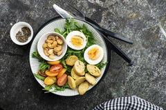 Φρέσκια σαλάτα άνοιξη με το βρασμένο αυγό, το arugula, τη σαλάτα, τις ντομάτες, τα πεκάν και τριζάτα ψημένα croutons ψωμιού σε έν Στοκ φωτογραφίες με δικαίωμα ελεύθερης χρήσης