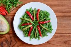 Φρέσκια σαλάτα αβοκάντο, arugula και πιπεριών Πράσινη σαλάτα arugula και αβοκάντο με το φρέσκο πιπέρι και σουσάμι σε ένα άσπρο πι Στοκ φωτογραφίες με δικαίωμα ελεύθερης χρήσης