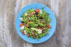 Φρέσκια σαλάτα - εύγευστη φρέσκια σαλάτα με τις ντομάτες, μαρούλι, μελιτζάνα, κολοκύθια, τυρί, ζαμπόν της Πάρμας και ελαιόλαδο, μ Στοκ Φωτογραφία
