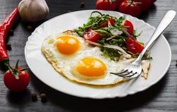 Φρέσκια σαλάτα και δύο τηγανισμένα αυγά στο σκοτεινό ξύλινο υπόβαθρο Στοκ Φωτογραφίες