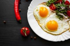 Φρέσκια σαλάτα και δύο τηγανισμένα αυγά στο σκοτεινό ξύλινο υπόβαθρο Στοκ εικόνα με δικαίωμα ελεύθερης χρήσης