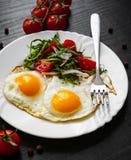 Φρέσκια σαλάτα και δύο τηγανισμένα αυγά στο σκοτεινό ξύλινο υπόβαθρο Στοκ Φωτογραφία