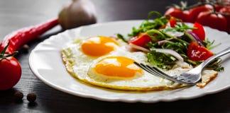 Φρέσκια σαλάτα και δύο τηγανισμένα αυγά στο σκοτεινό ξύλινο υπόβαθρο Στοκ φωτογραφία με δικαίωμα ελεύθερης χρήσης
