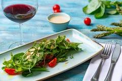 Φρέσκια σαλάτα με τις ντομάτες και τα μικτά πράσινα arugula, mesclun, mache στο ξύλινο υπόβαθρο τρόφιμα υγιή Στοκ Εικόνες