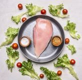 Φρέσκια σαλάτα με τις ντομάτες κερασιών, καρυκεύματα και χορτάρια, με το ακατέργαστο στήθος κοτόπουλου σε έναν παν τρύγο, ξύλινο  Στοκ Εικόνες