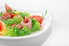Φρέσκια σαλάτα με τις ντομάτες, το arugula, το τυρί και το ζαμπόν στο άσπρο πιάτο και το άσπρο υπόβαθρο Στοκ εικόνα με δικαίωμα ελεύθερης χρήσης