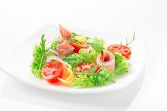 Φρέσκια σαλάτα με τις ντομάτες, το arugula, το τυρί και το ζαμπόν στο άσπρο πιάτο και το άσπρο υπόβαθρο Στοκ Εικόνες