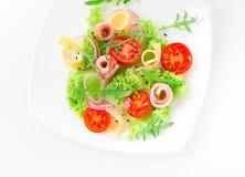 Φρέσκια σαλάτα με τις ντομάτες, το arugula, το τυρί και το ζαμπόν στο άσπρο πιάτο και το άσπρο υπόβαθρο Στοκ φωτογραφία με δικαίωμα ελεύθερης χρήσης