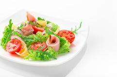 Φρέσκια σαλάτα με τις ντομάτες, το arugula, το τυρί και το ζαμπόν στο άσπρο πιάτο και το άσπρο υπόβαθρο Στοκ φωτογραφίες με δικαίωμα ελεύθερης χρήσης