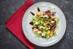 Φρέσκια σαλάτα με το arugula, το τυρί, τα μανιτάρια και τα καρύδια στο σκοτεινό υπόβαθρο πετρών Στοκ φωτογραφία με δικαίωμα ελεύθερης χρήσης