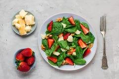 Φρέσκια σαλάτα φραουλών με τα φύλλα σπανακιού, το τυρί παρμεζάνας και τα ξύλα καρυδιάς με το δίκρανο υγιή keto τρόφιμα διατροφής στοκ εικόνες με δικαίωμα ελεύθερης χρήσης