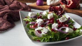 Φρέσκια σαλάτα άνοιξη με το τυρί φέτας, το κόκκινους κρεμμύδι και τους σπόρους ροδιών στο άσπρο πιάτο στο ξύλινο υπόβαθρο Στοκ Εικόνα