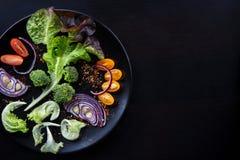 Φρέσκια σαλάτα με τα λαχανικά σε ένα μαύρο πιάτο Στοκ Φωτογραφίες