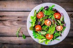 Φρέσκια σαλάτα με τα μικτά πράσινα και ντομάτα κερασιών στο ξύλινο υπόβαθρο Στοκ Εικόνες