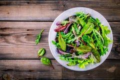 Φρέσκια σαλάτα με τα μικτά πράσινα στο ξύλινο υπόβαθρο Στοκ φωτογραφία με δικαίωμα ελεύθερης χρήσης