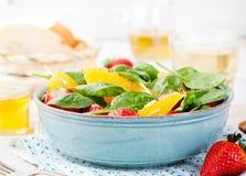 Φρέσκια σαλάτα με τη φράουλα, το πορτοκάλι και το σπανάκι σε ένα κύπελλο στο ξύλινο υπόβαθρο Στοκ Φωτογραφίες