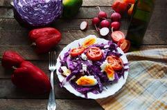 Φρέσκια σαλάτα με τις ντομάτες κερασιών, σπανάκι, σε ένα πιάτο στο ξύλινο υπόβαθρο, σαλάτα με τα λαχανικά και τα πράσινα, sala φρ Στοκ Φωτογραφίες