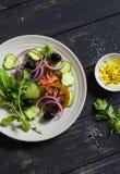 Φρέσκια σαλάτα με τις ντομάτες, τα αγγούρια και τις ελιές σε ένα άσπρο πιάτο Στοκ φωτογραφία με δικαίωμα ελεύθερης χρήσης