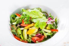 Φρέσκια σαλάτα με το κουνουπίδι, arugula, μαρούλι, ντομάτες κερασιών, αγγούρι, γλυκό πιπέρι στο ξύλινο υπόβαθρο Στοκ Εικόνες