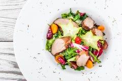 Φρέσκια σαλάτα με το στήθος, το arugula, το μαρούλι, το κουνουπίδι, τα physalis και το carambola κοτόπουλου στο πιάτο ξύλινο στεν Στοκ Εικόνα