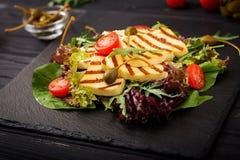 Φρέσκια σαλάτα με το ψημένο στη σχάρα τυρί, ντομάτες, κάπαρες, μαρούλι στοκ εικόνα