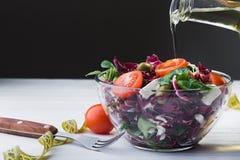 Φρέσκια σαλάτα στο κύπελλο γυαλιού με χυμένο το ντομάτα ελαιόλαδο Στοκ Φωτογραφία